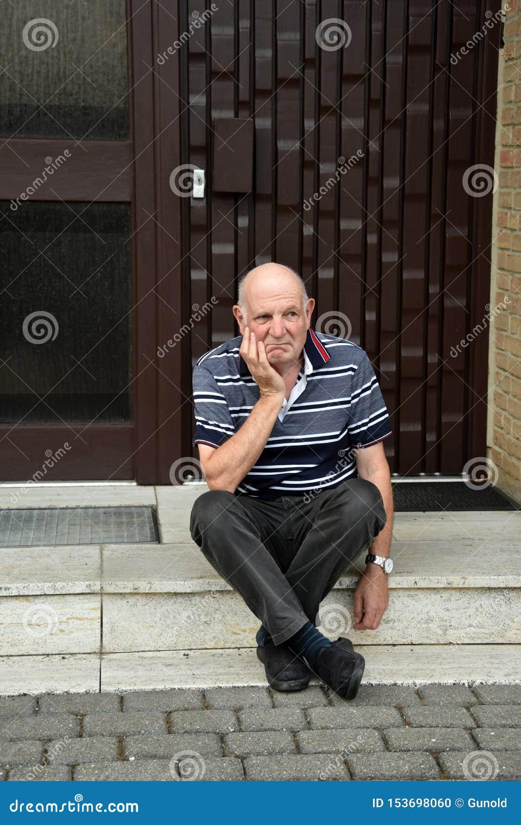 Homme supérieur verrouillé s asseyant devant sa maison