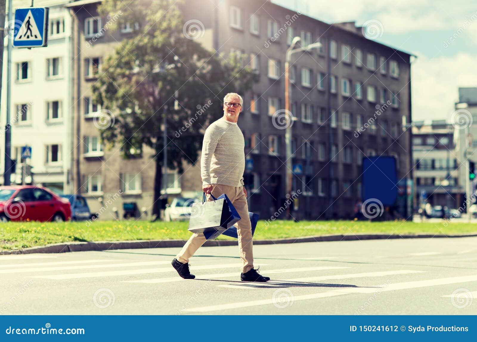 Homme sup?rieur avec des paniers marchant sur le passage pi?ton