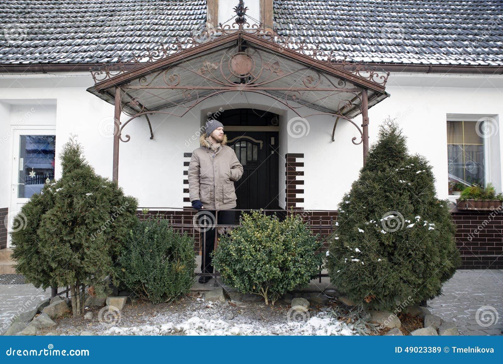 Le Porche De La Maison homme sur un porche de la maison blanche de village avec les