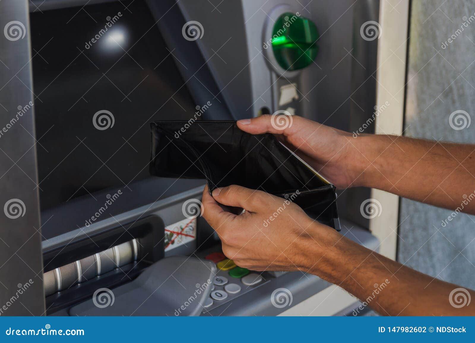 Homme tenant le portefeuille vide près de la machine d atmosphère Le concept d ?tre s est cass?
