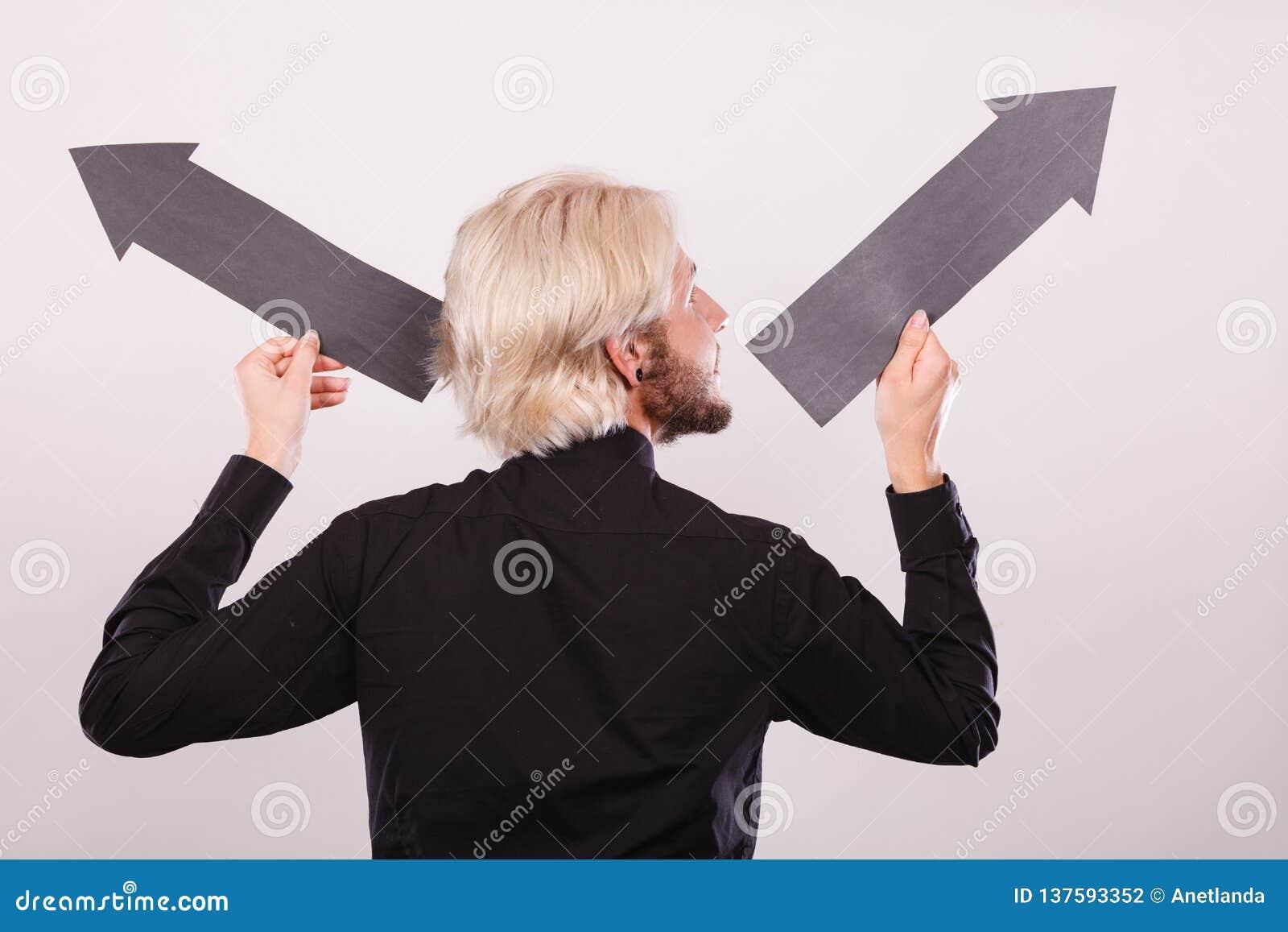 Homme tenant les flèches noires se dirigeant à gauche et à droite