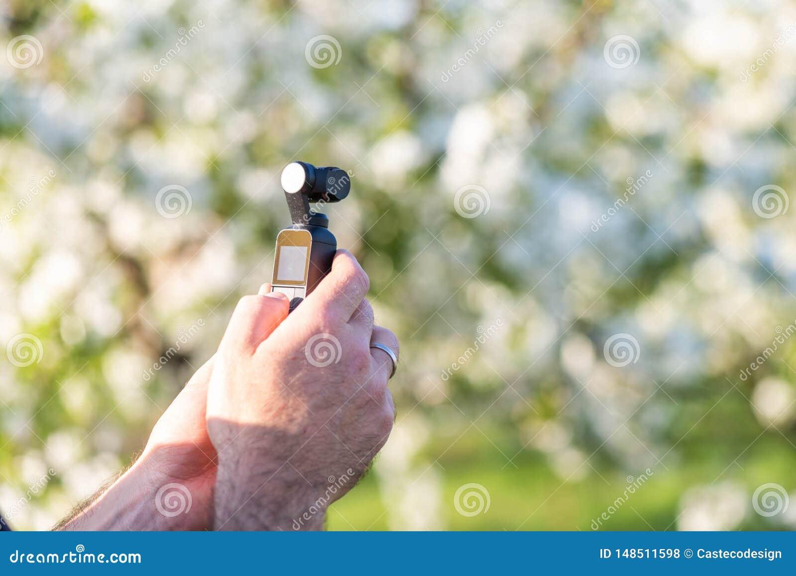 Homme tenant une caméra vidéo moderne minuscule en parc Idées de pelliculage de printemps