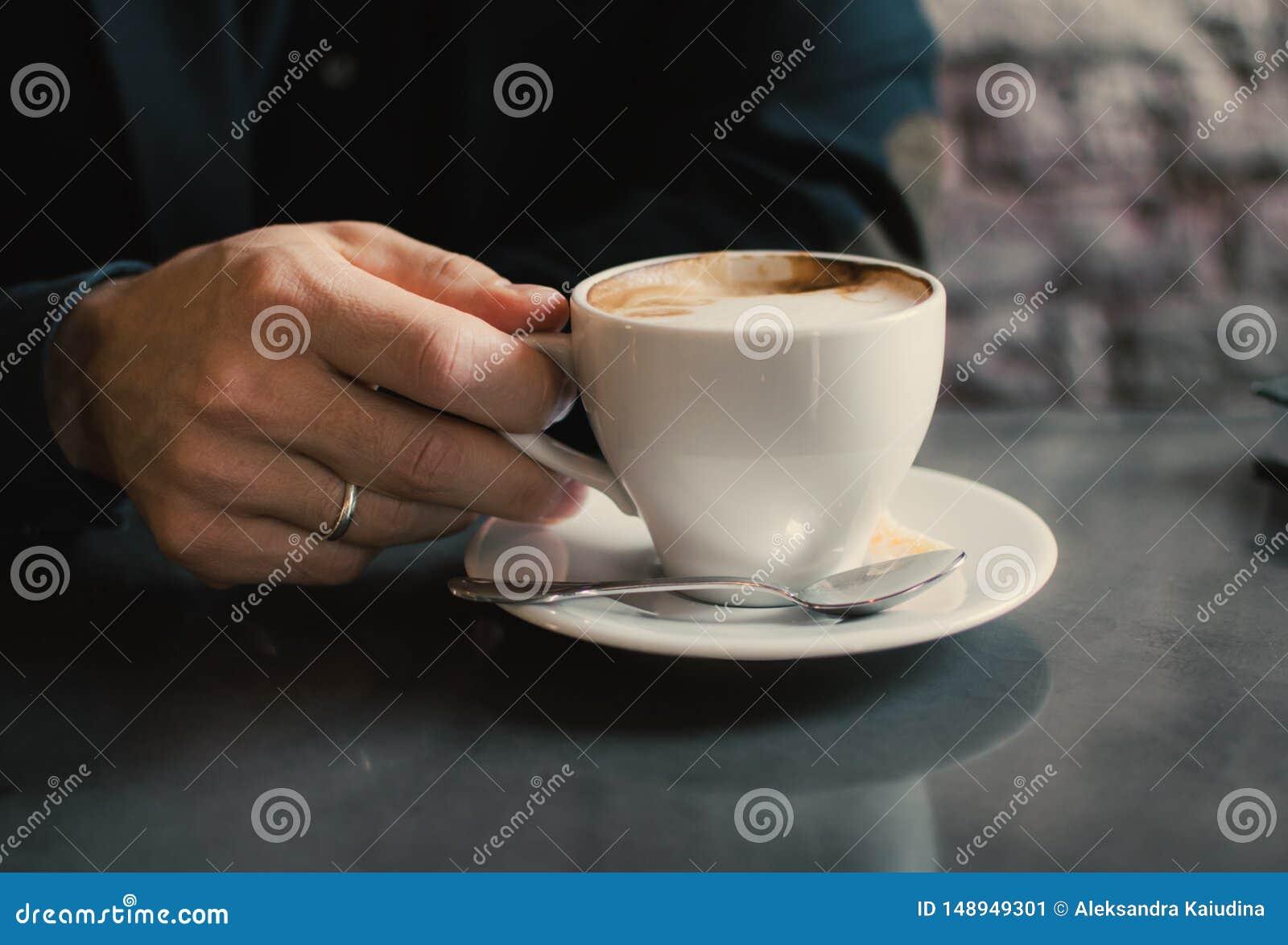 Homme tenant une tasse de cappuccino