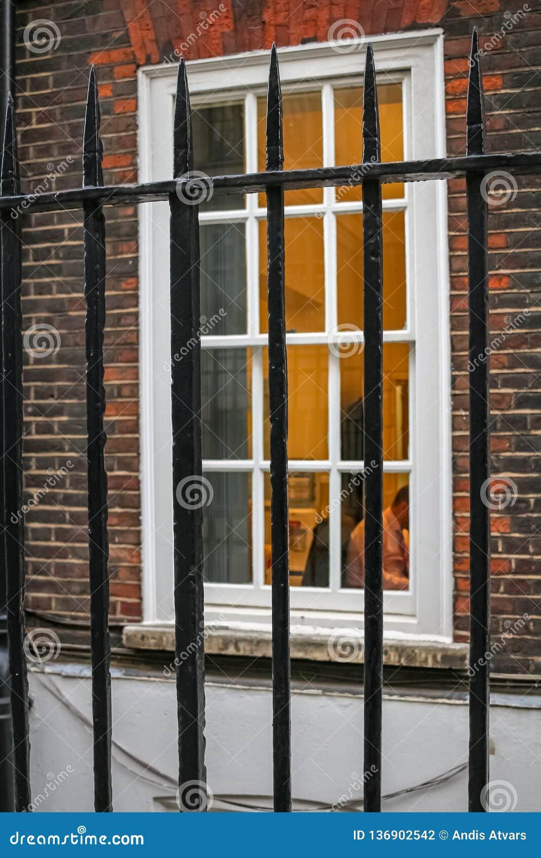 Homme travaillant à la vue de bureau par des grilles Les gens sont soumis à une contrainte parce qu ils sont emprisonnés en heure