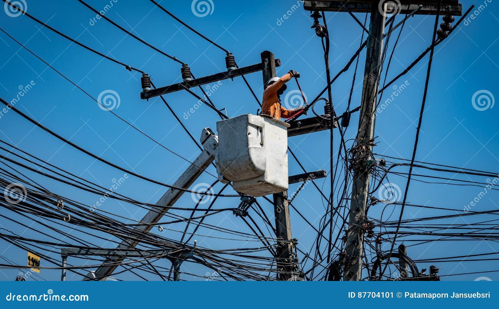Homme travaillant avec le poteau de ligne électrique