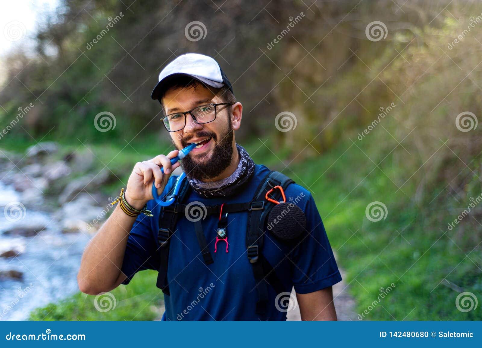 Homme trimardant et hydratant avec la conduite d eau