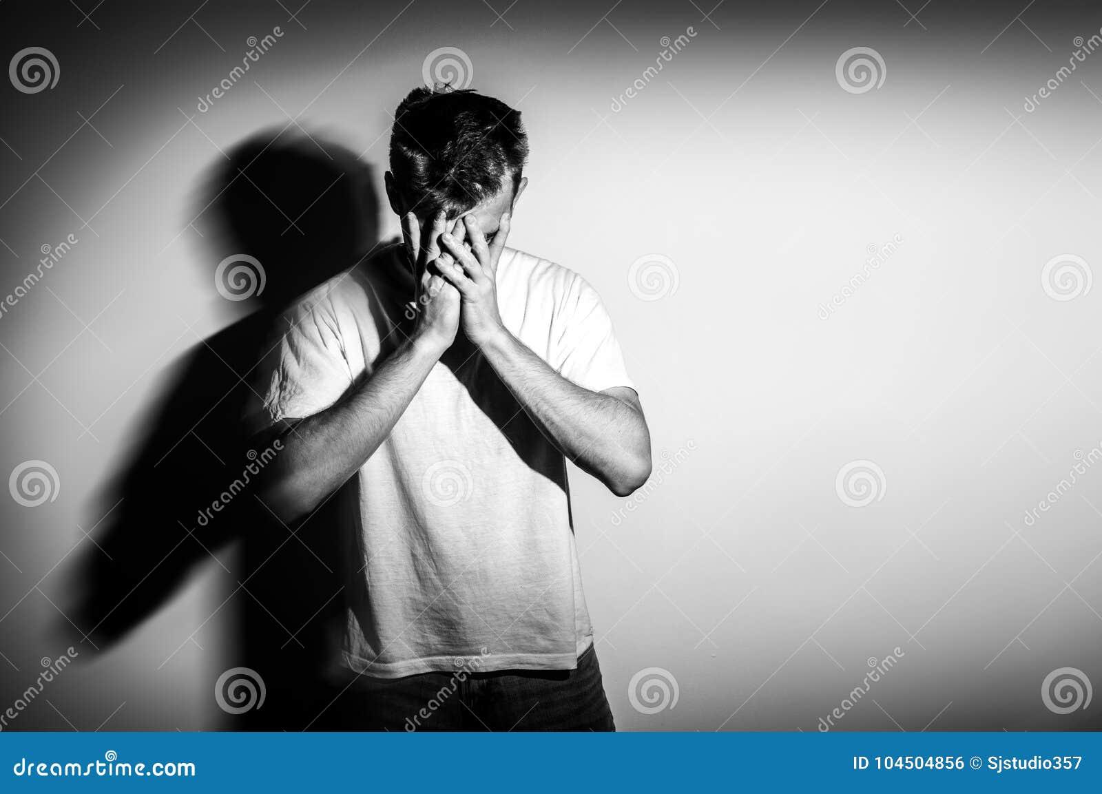 Homme triste avec des mains sur le visage dans la tristesse, sur le fond blanc, photo noire et blanche, l espace libre