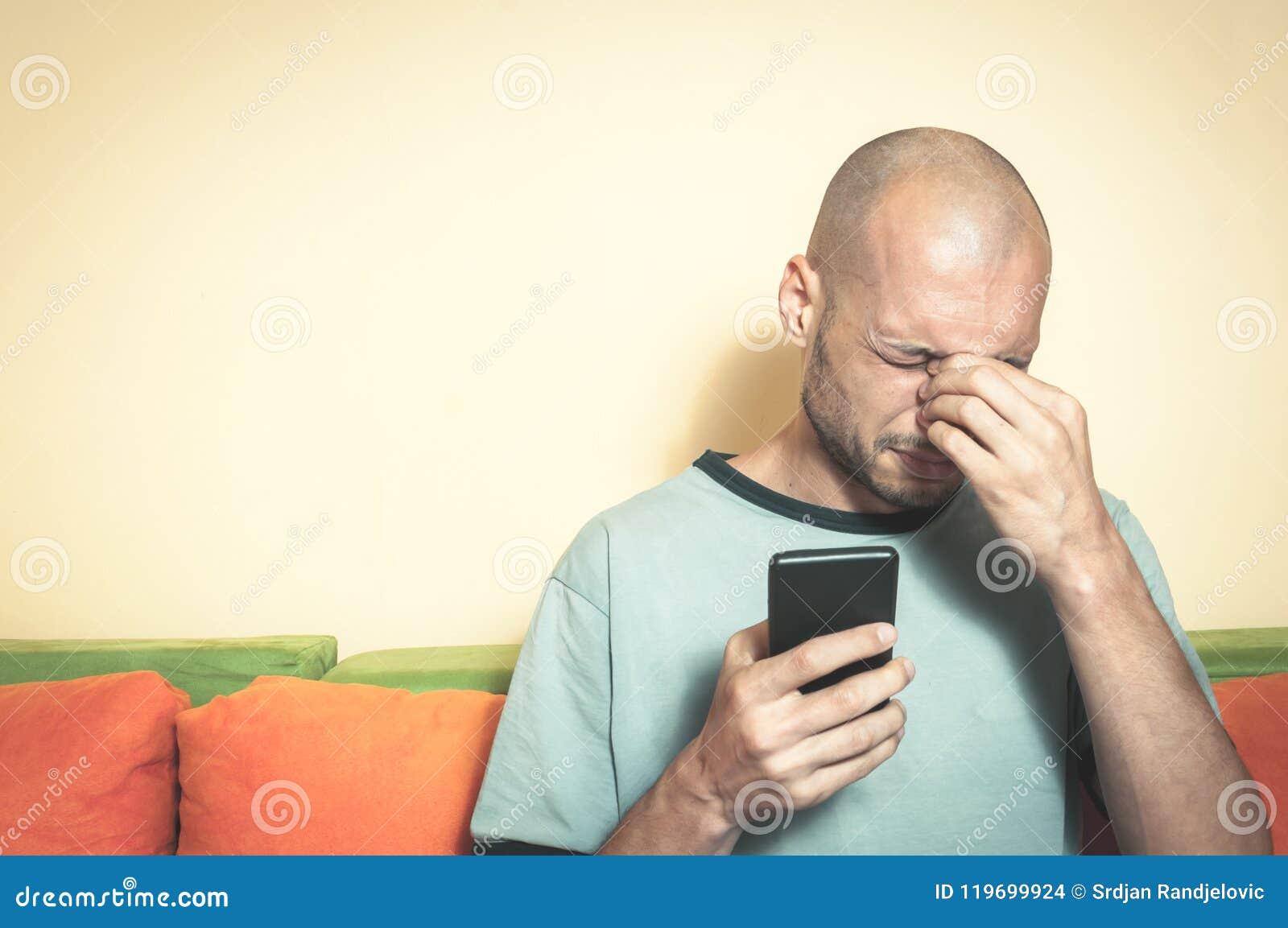 Homme triste tenant son téléphone portable dans des ses mains et cri parce que son amie se cassent avec lui au-dessus du message