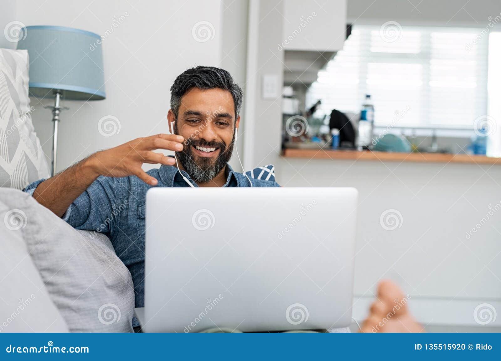 Homme utilisant l ordinateur portable pour l appel visuel