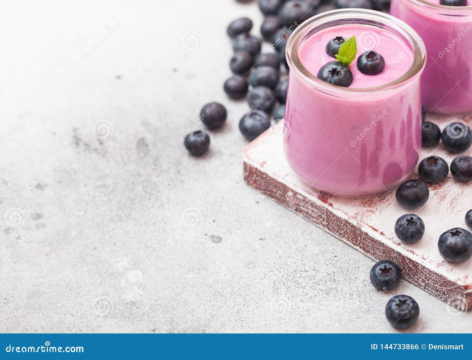 新hommemade乳脂状的蓝莓酸奶用在葡萄酒木板的新鲜的蓝莓在石厨房用桌背景