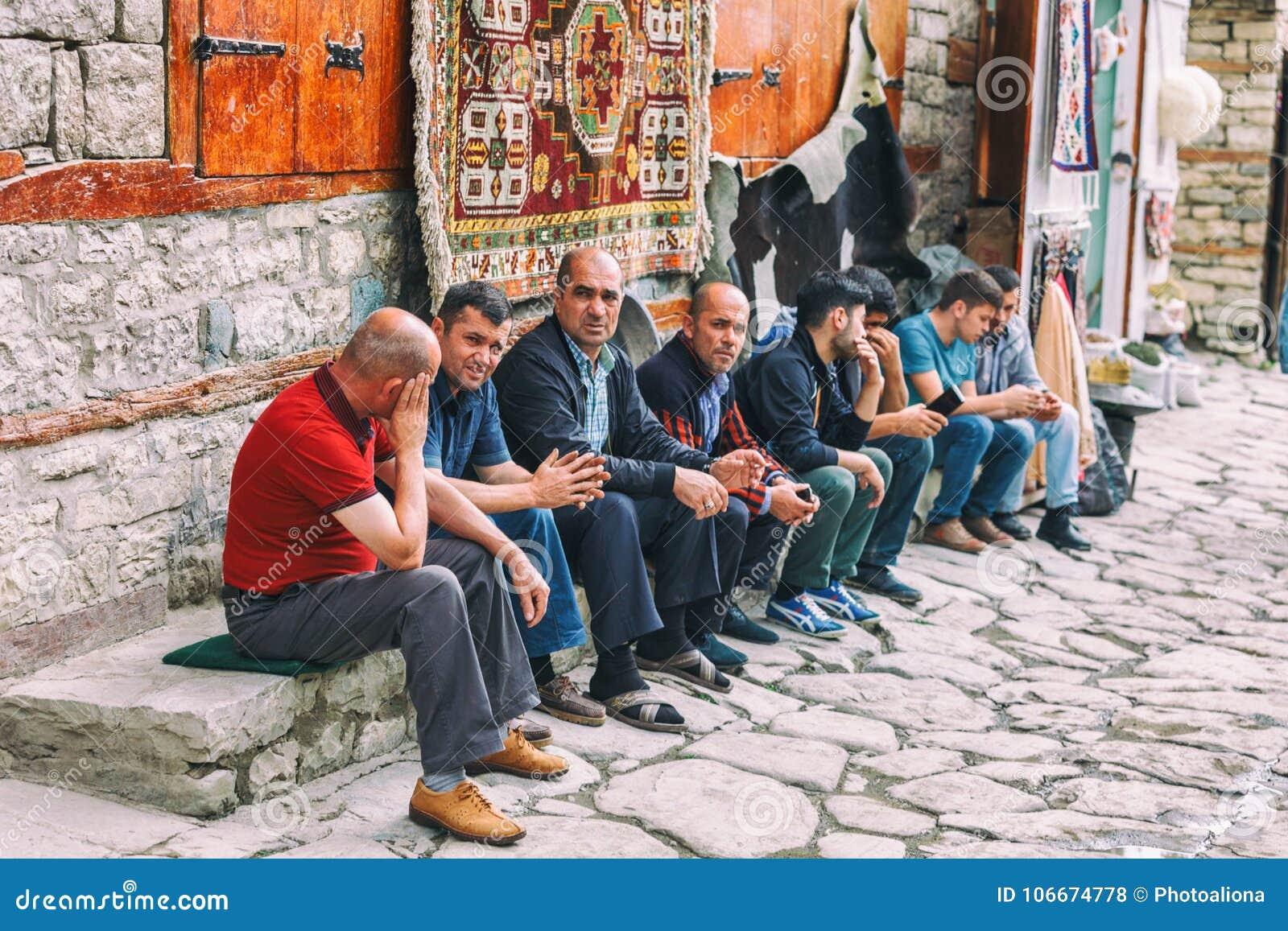 Hommes azéris s asseyant et parlant dans la rue sur la rue de Huseynov de pavé rond, la rue principale du village montagneux de L