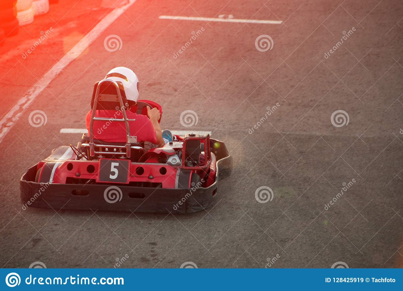 Hommes conduisant la voiture de kart avec la vitesse dans une voie d emballage de terrain de jeu