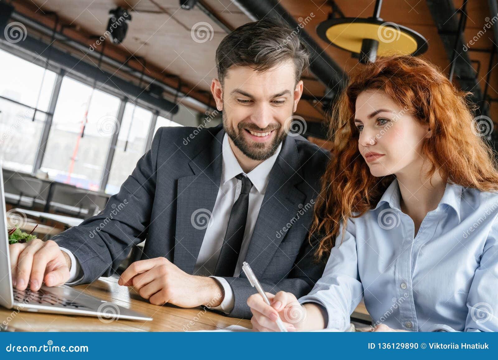 Hommes d affaires ayant le déjeuner d affaires à l ordinateur portable se reposant de lecture rapide d homme de restaurant regard