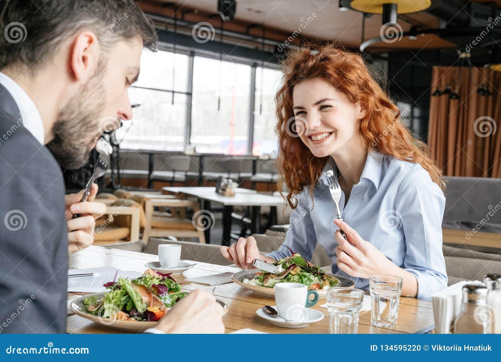 Hommes d affaires ayant le déjeuner d affaires au restaurant reposant la salade mangeuse d hommes concentrée tandis que rire de f