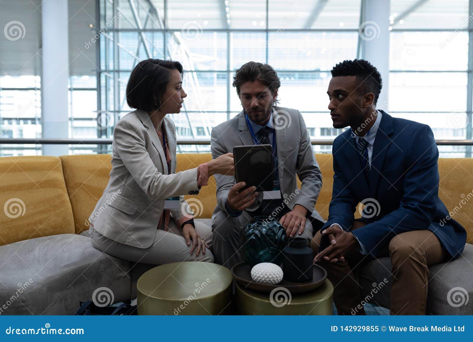 Hommes d affaires multi-ethniques s asseyant et discutant au-dessus du comprimé numérique dans le lobby au bureau