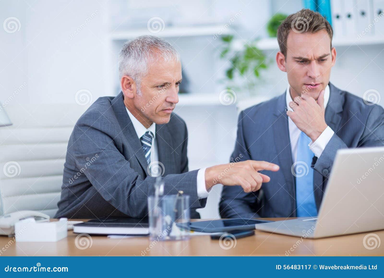 Hommes d affaires sérieux travaillant ensemble sur l ordinateur portable