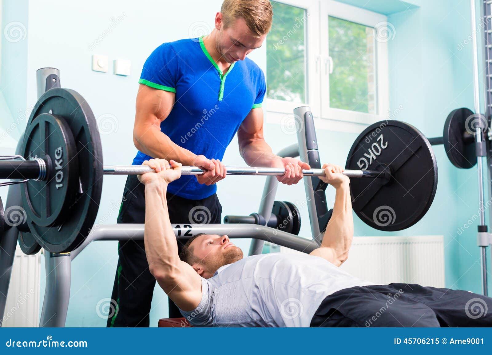 Hommes dans la formation de gymnase de sport avec le barbell