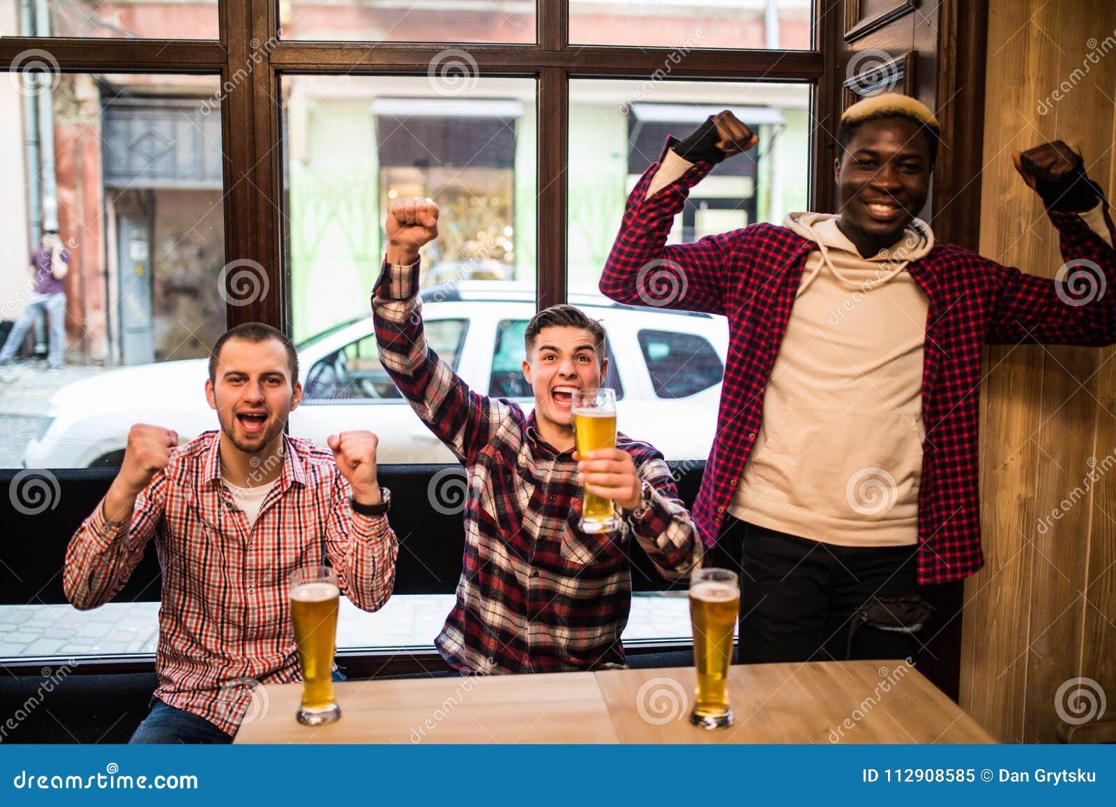 Hommes multiraciaux à la partie de football watcing de bar et à la bière potable