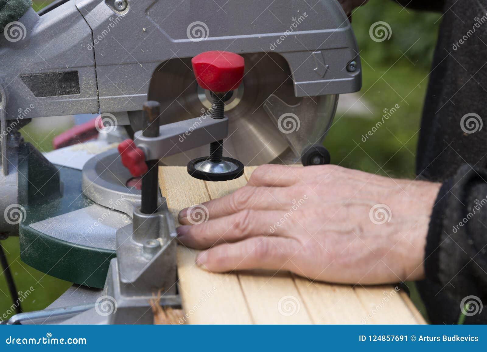 Hommes supérieurs préparant les matériaux en bois avec la scie rotatoire