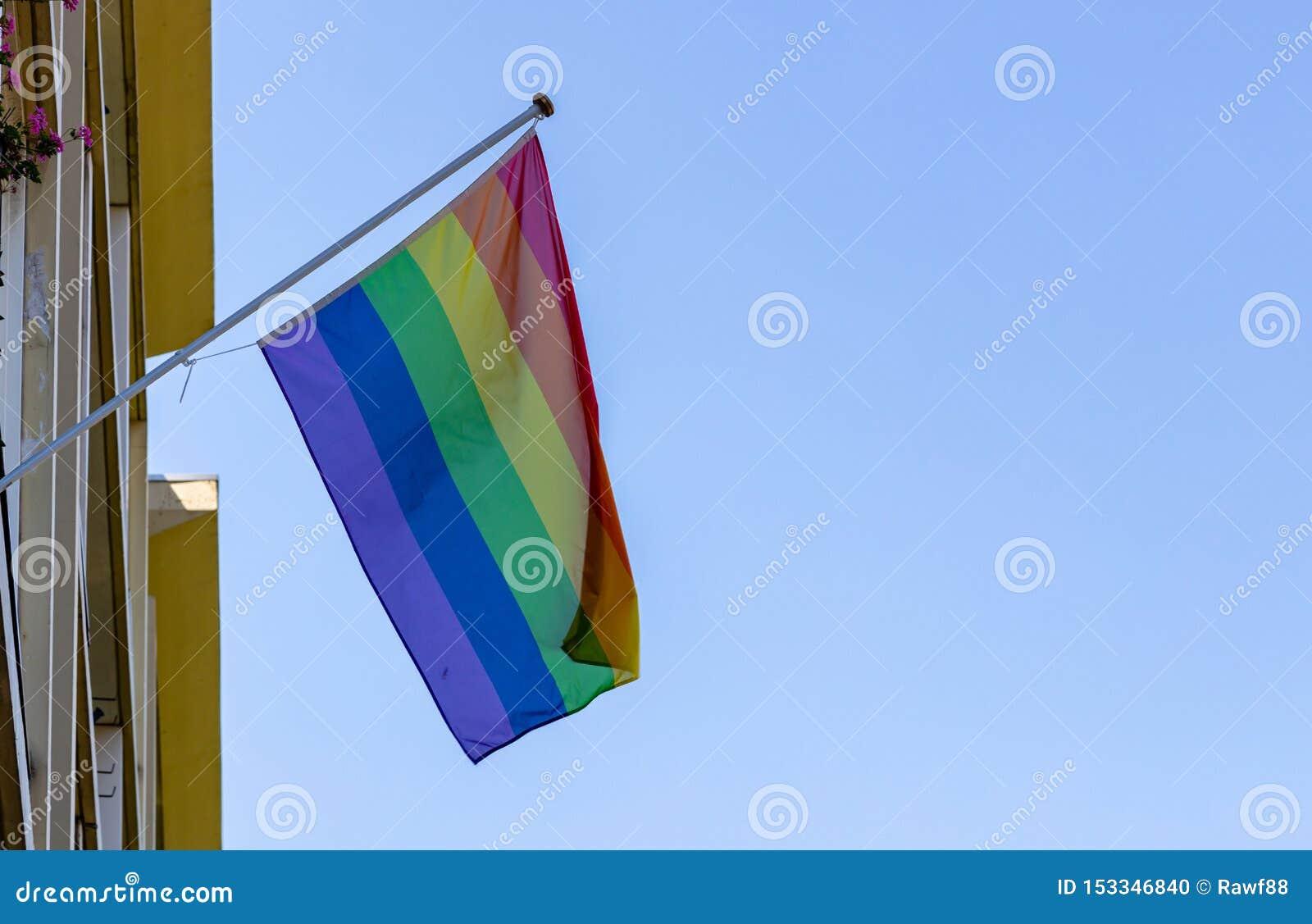Homoseksualnej dumy flagi falowanie przeciw jasnemu niebieskiemu niebu