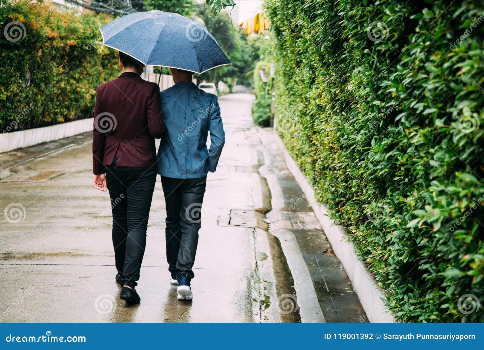 Homosexuelle Paare, die Regenschirm und Hände zusammenhalten Zurück von den homosexuellen Männern, die in den Regen gehen