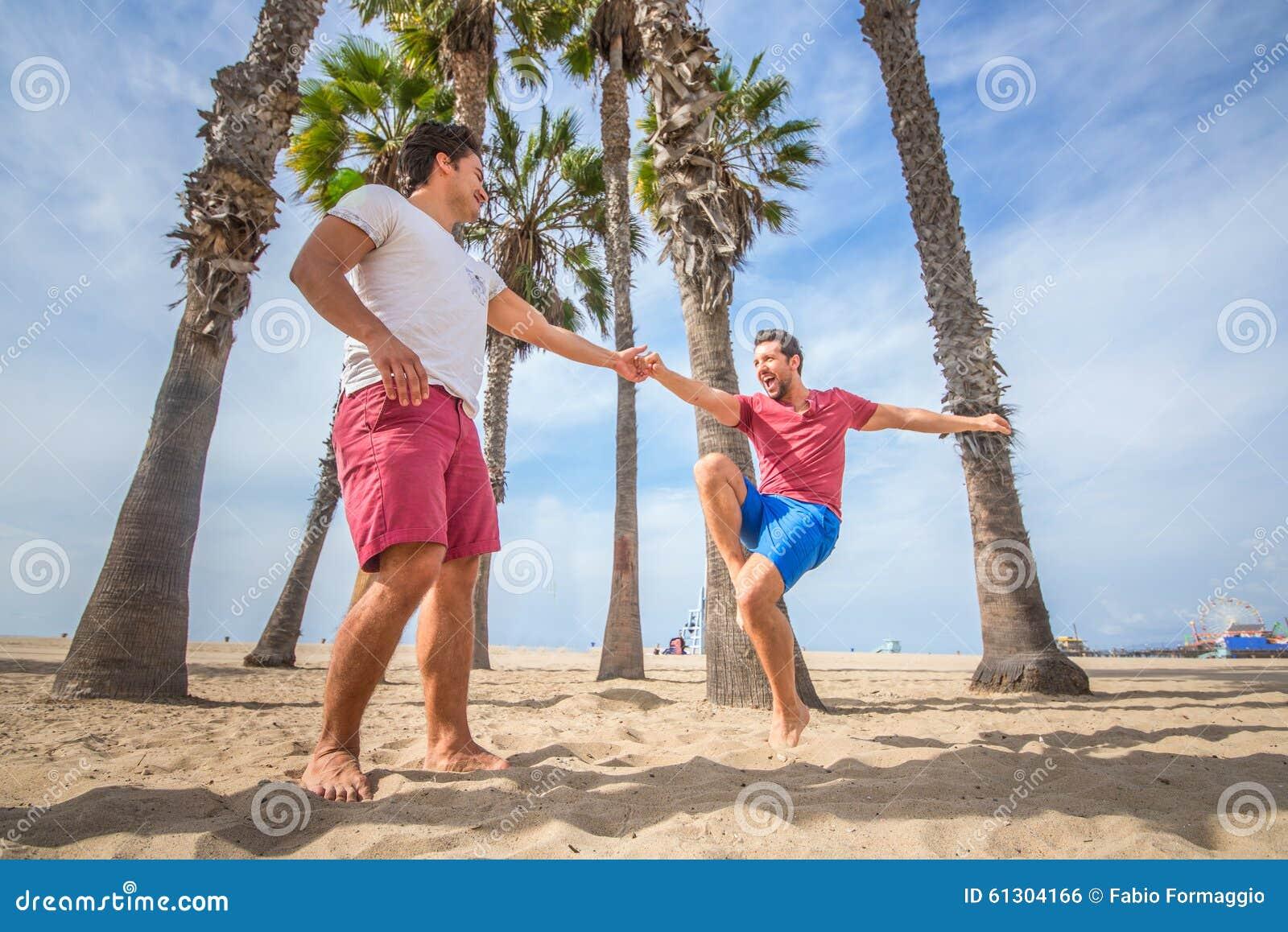 Homosexuelles Paartanzen auf dem Strand