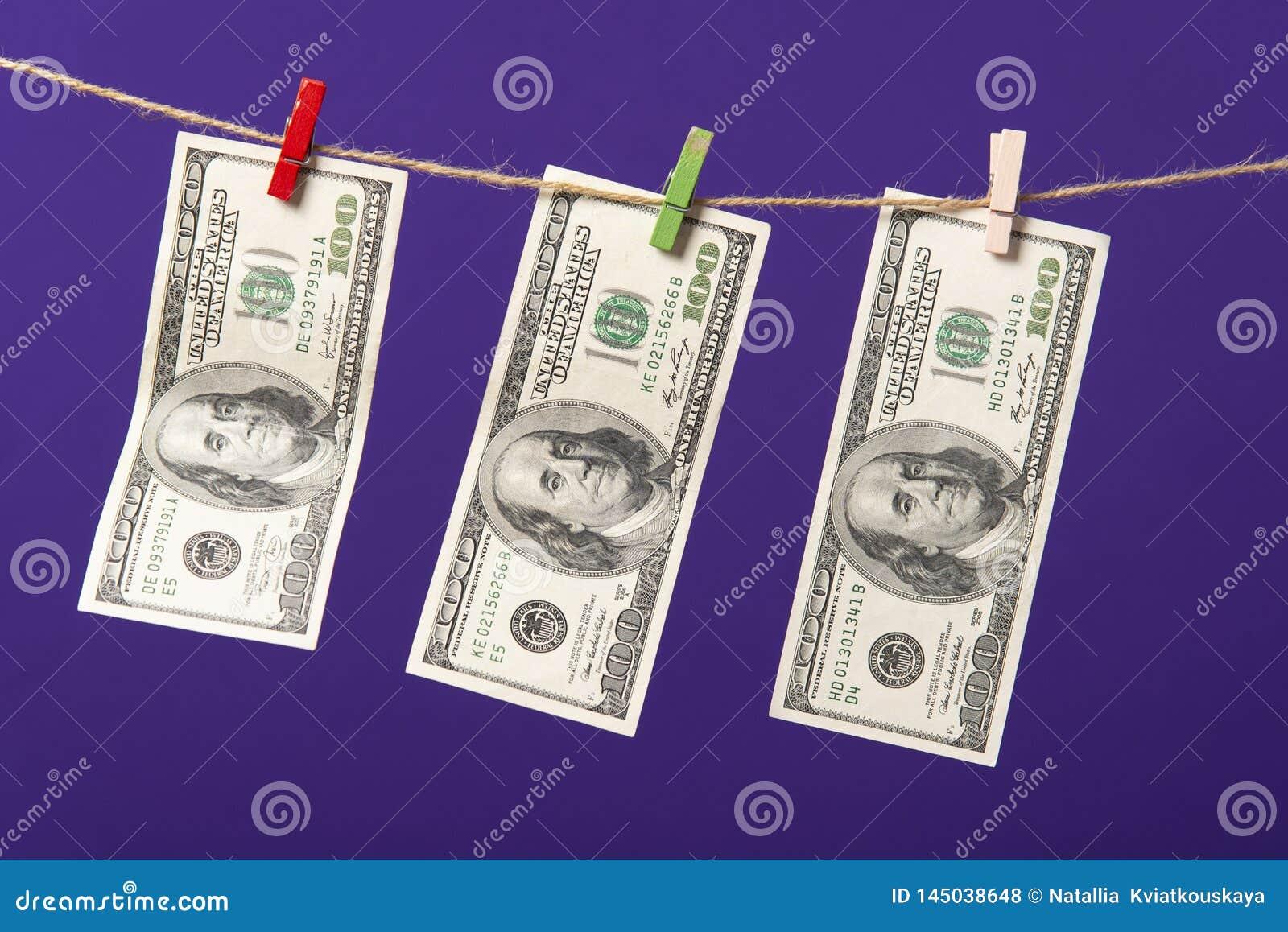 Honderd dollars die op drooglijn met houten klemmen op blauwe achtergrond hangen