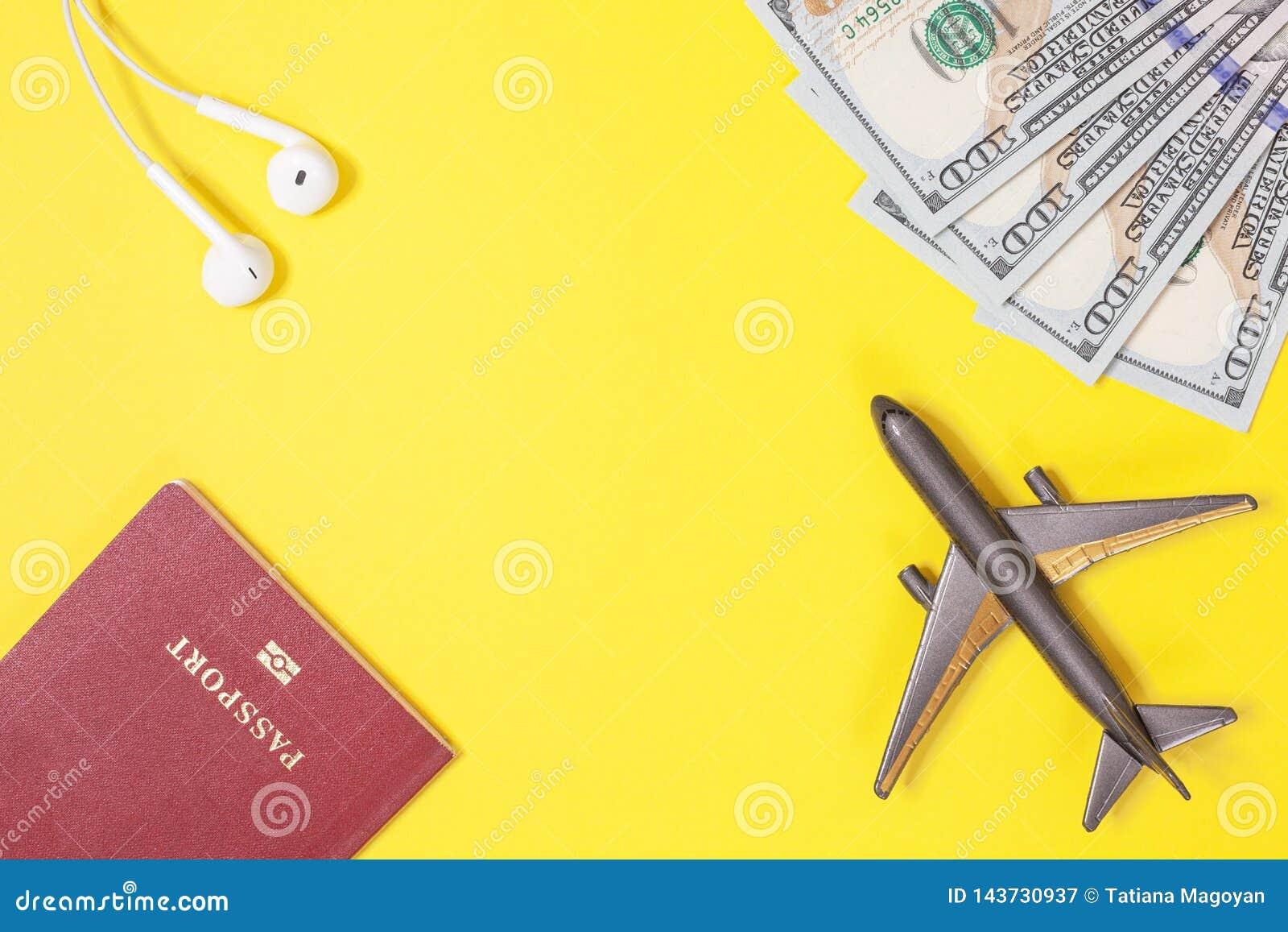 Honderd dollarsrekeningen, vliegtuig, hoofdtelefoons, buitenlands paspoort op heldere gele document achtergrond De ruimte van het