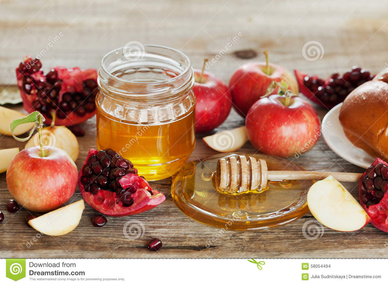 Honey, apple, pomegranate and bread hala, table set with traditional food for Jewish New Year Holiday, Rosh Hashana