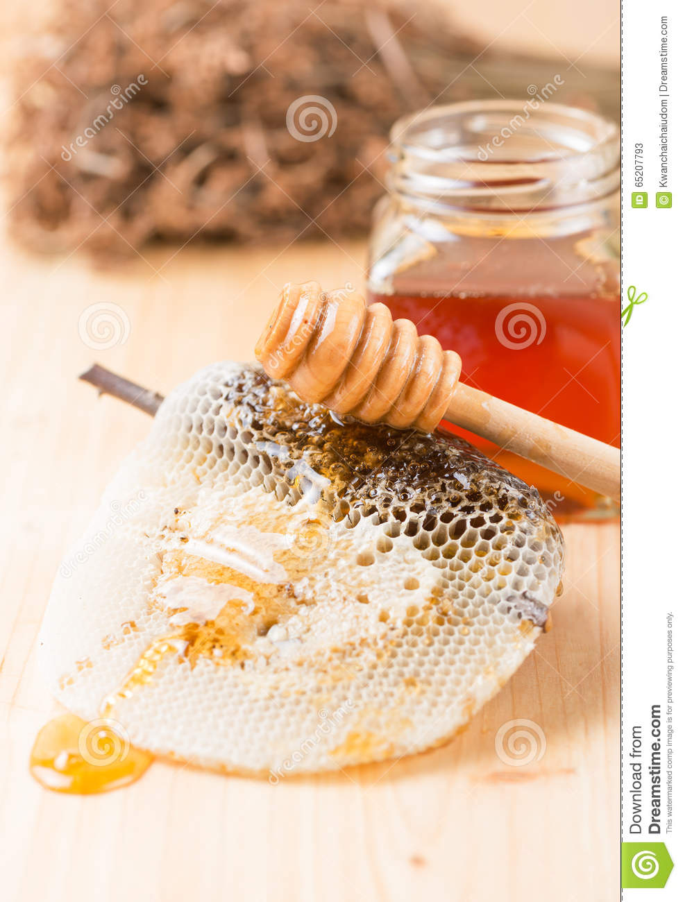 Honey dipper on the bee honeycomb