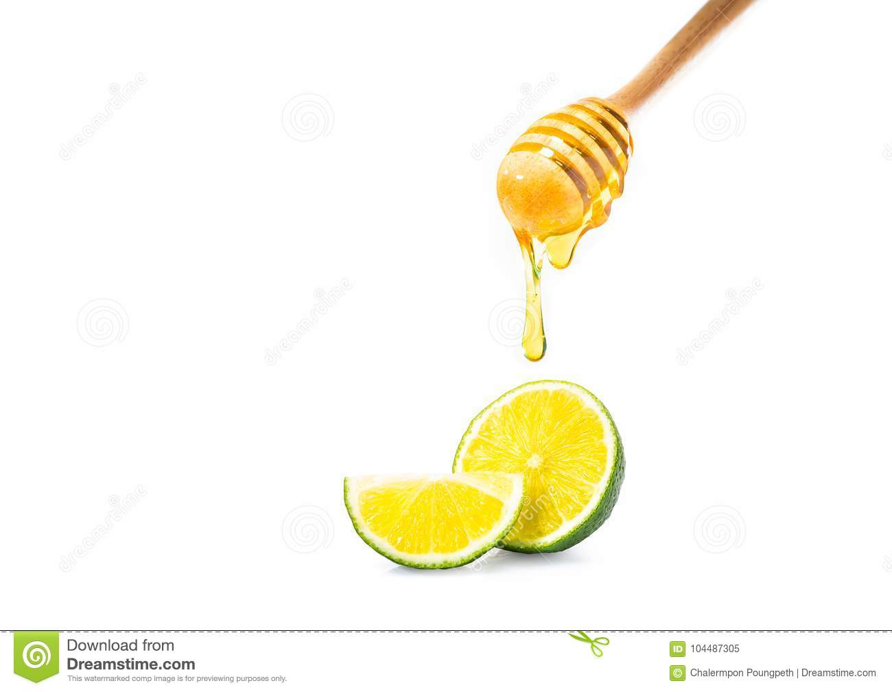 Honey dipper with honey dripping down, and cut fresh lime on iso