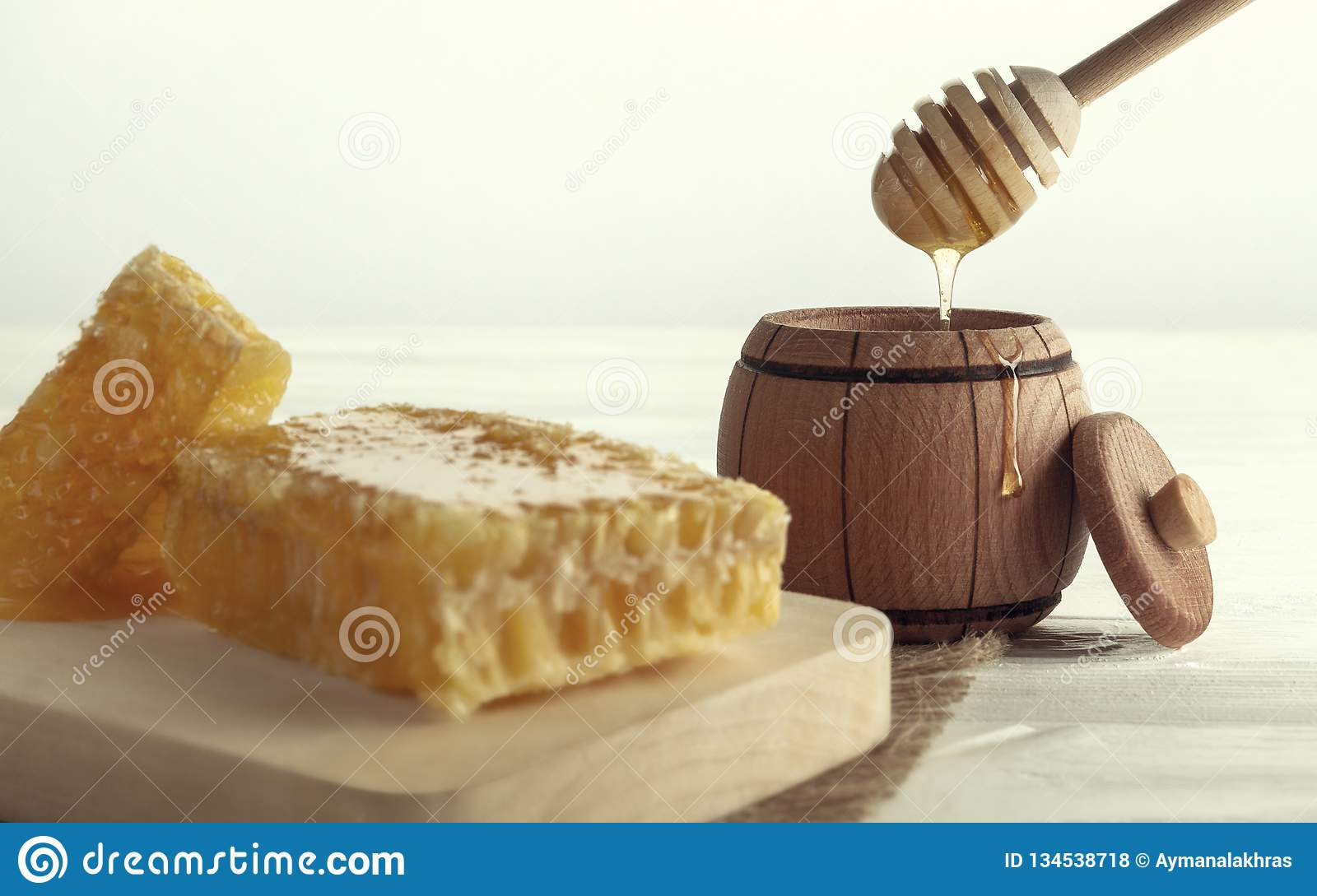 Honey dipper in Wooden jar and honey comb on wooden tray