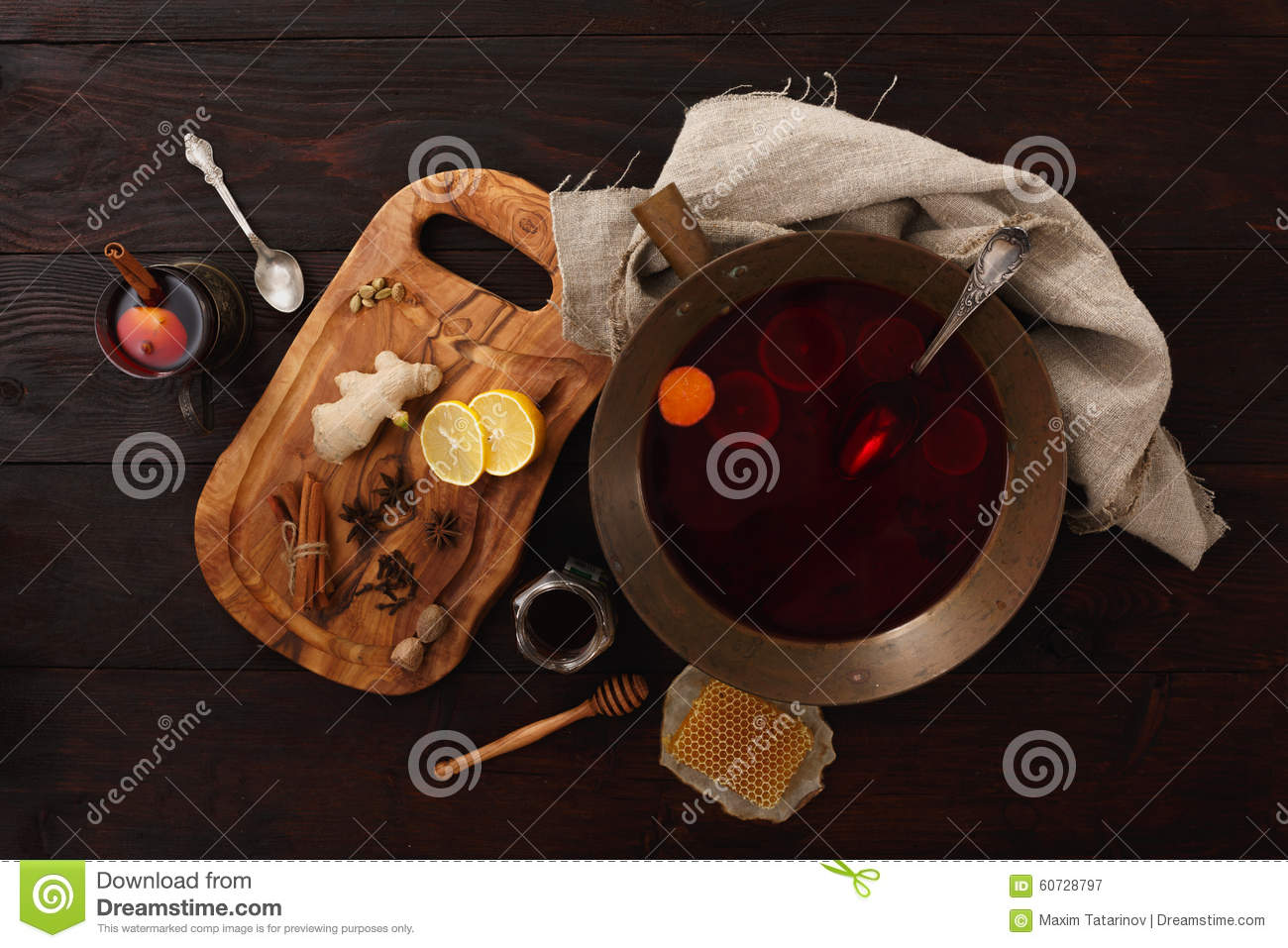 Honey ginger lemon mulled wine or punch in brass bowl over dark wooden ...