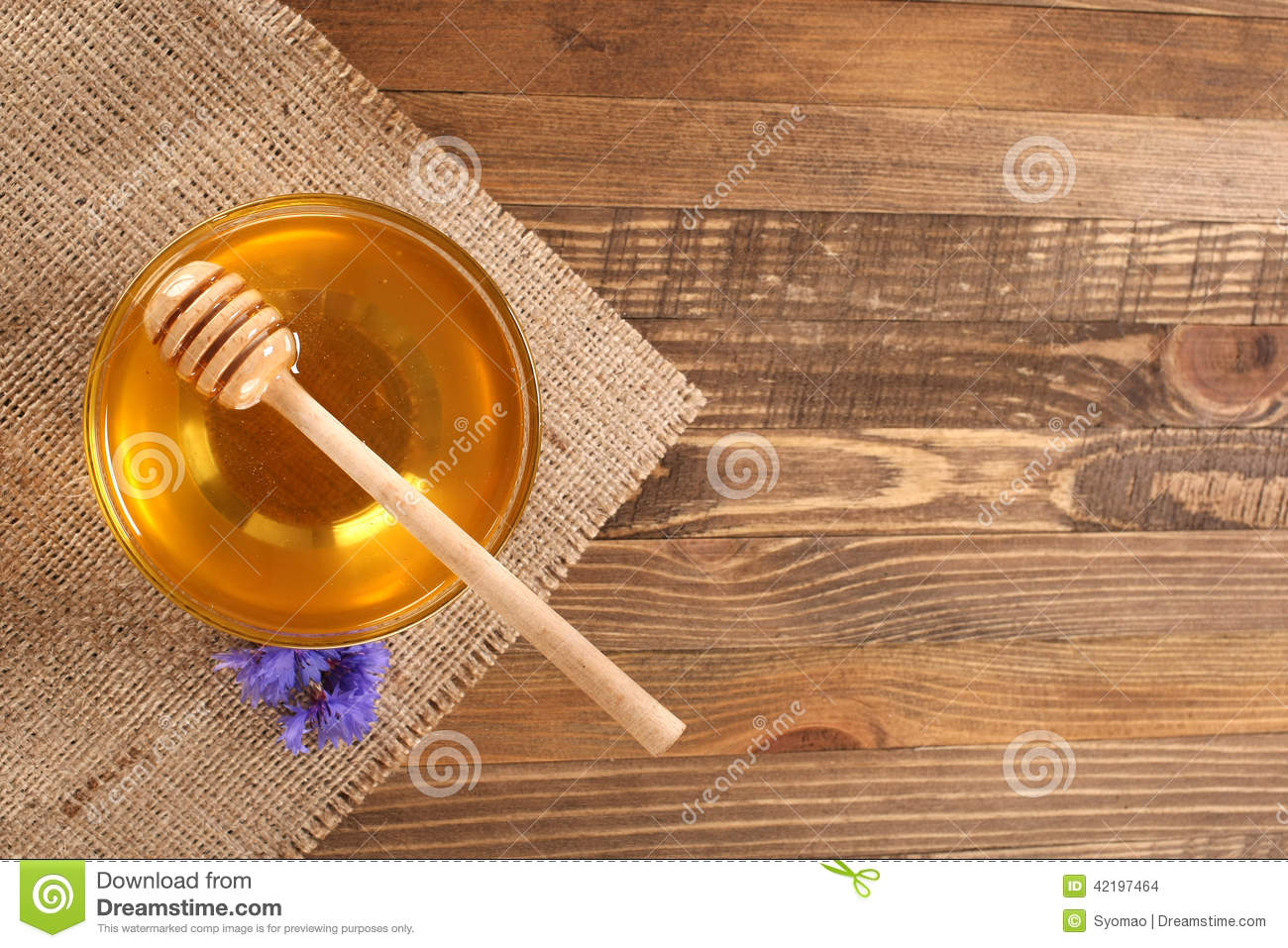 Honey in a glass bowl on a wooden boards background