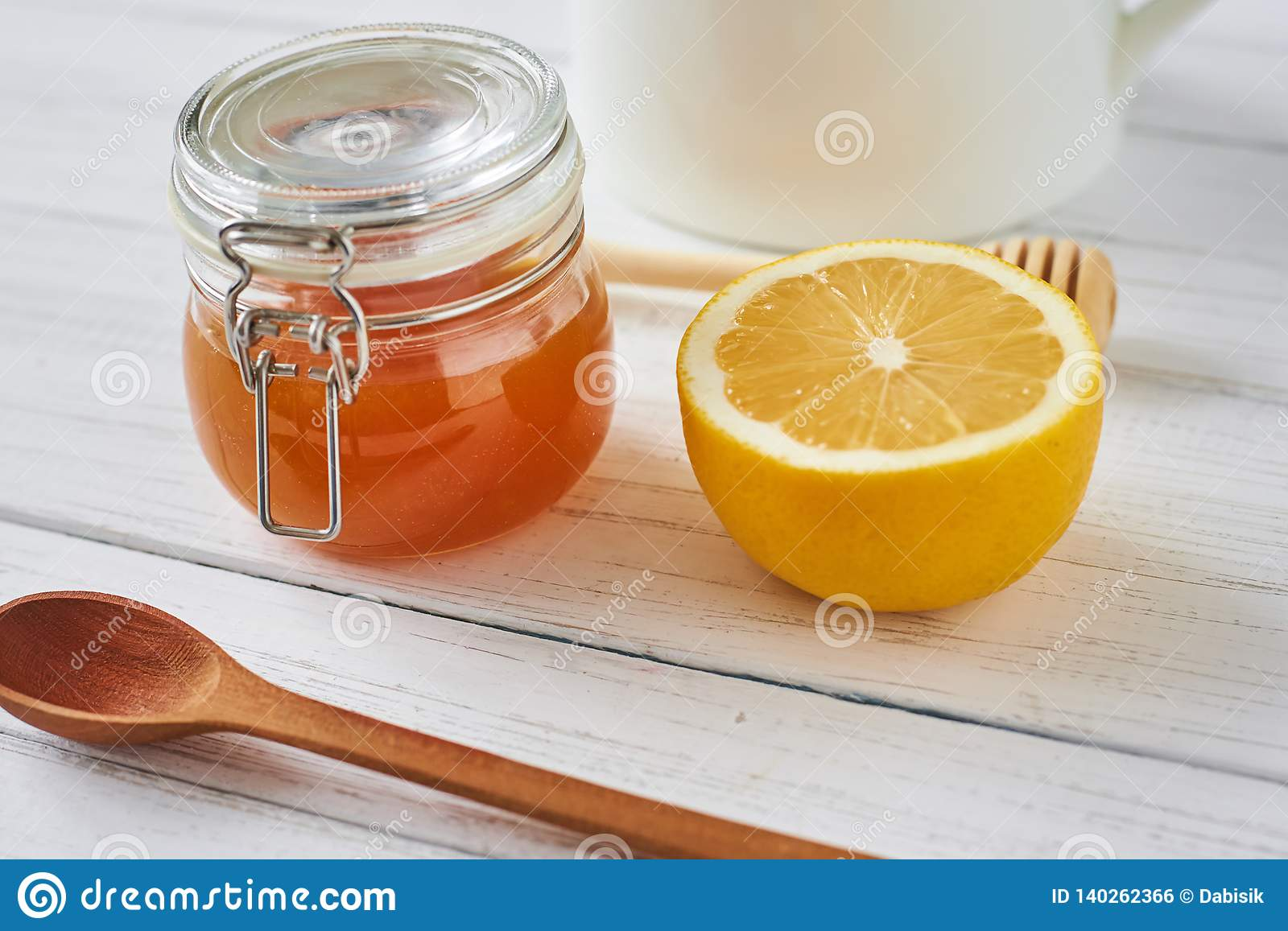 Honey in a glass jar and lemon on white background close up