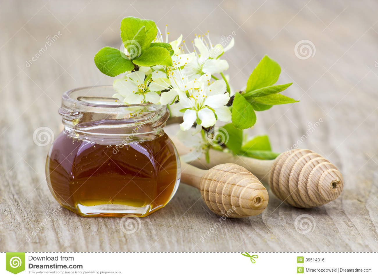 Honey in a jar, flowers and honey dippers