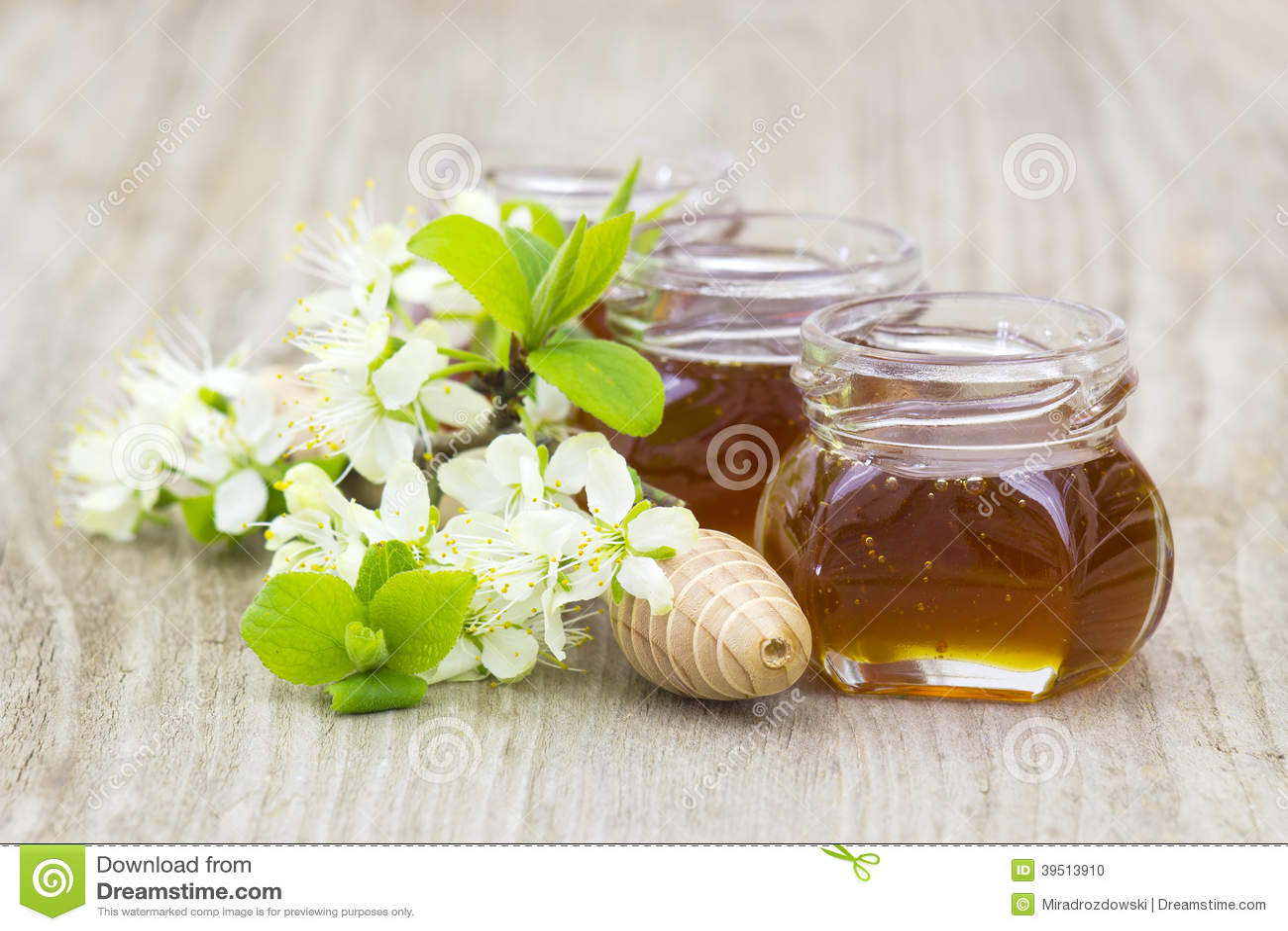 Honey in jars, flowers and honey dipper
