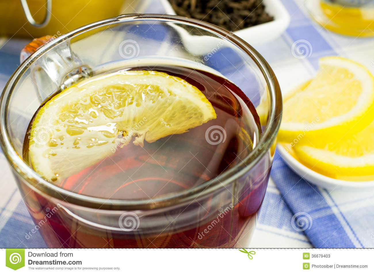 Cup of tea with a jar of honey and lemon slices on the table. Bowl ...