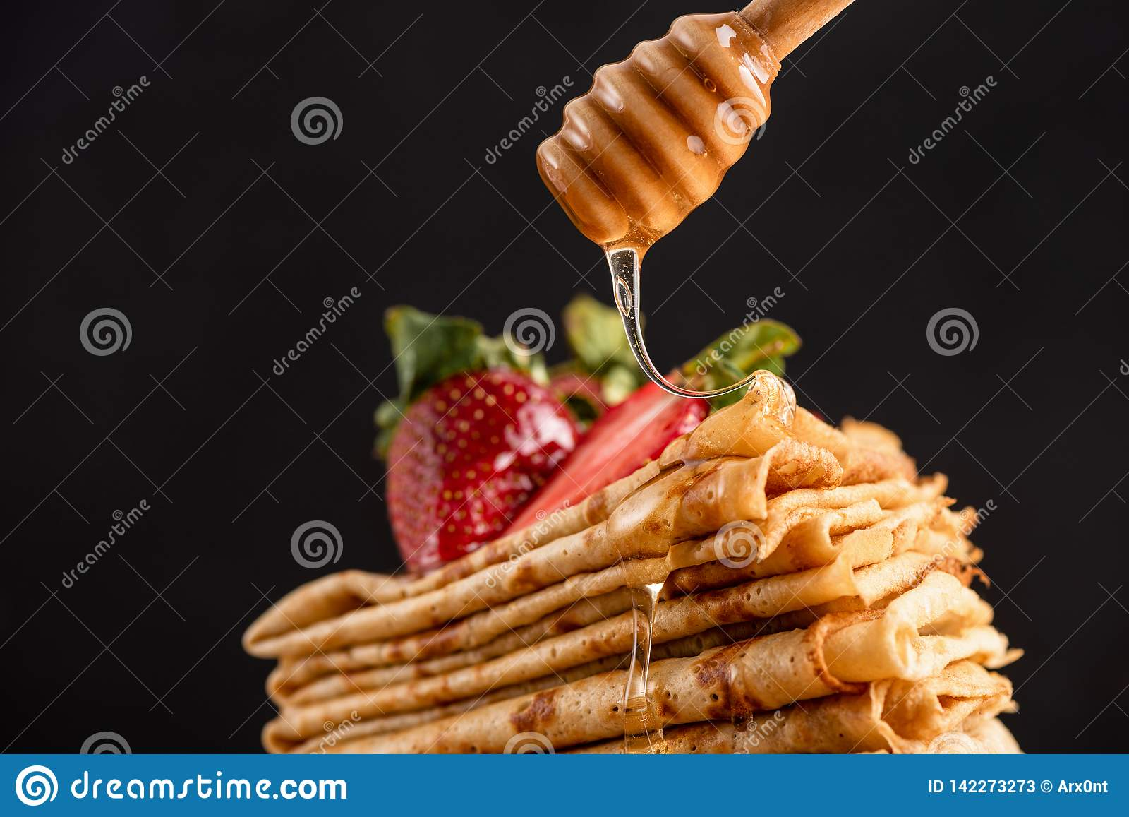 Honey pouring on crepes or blini