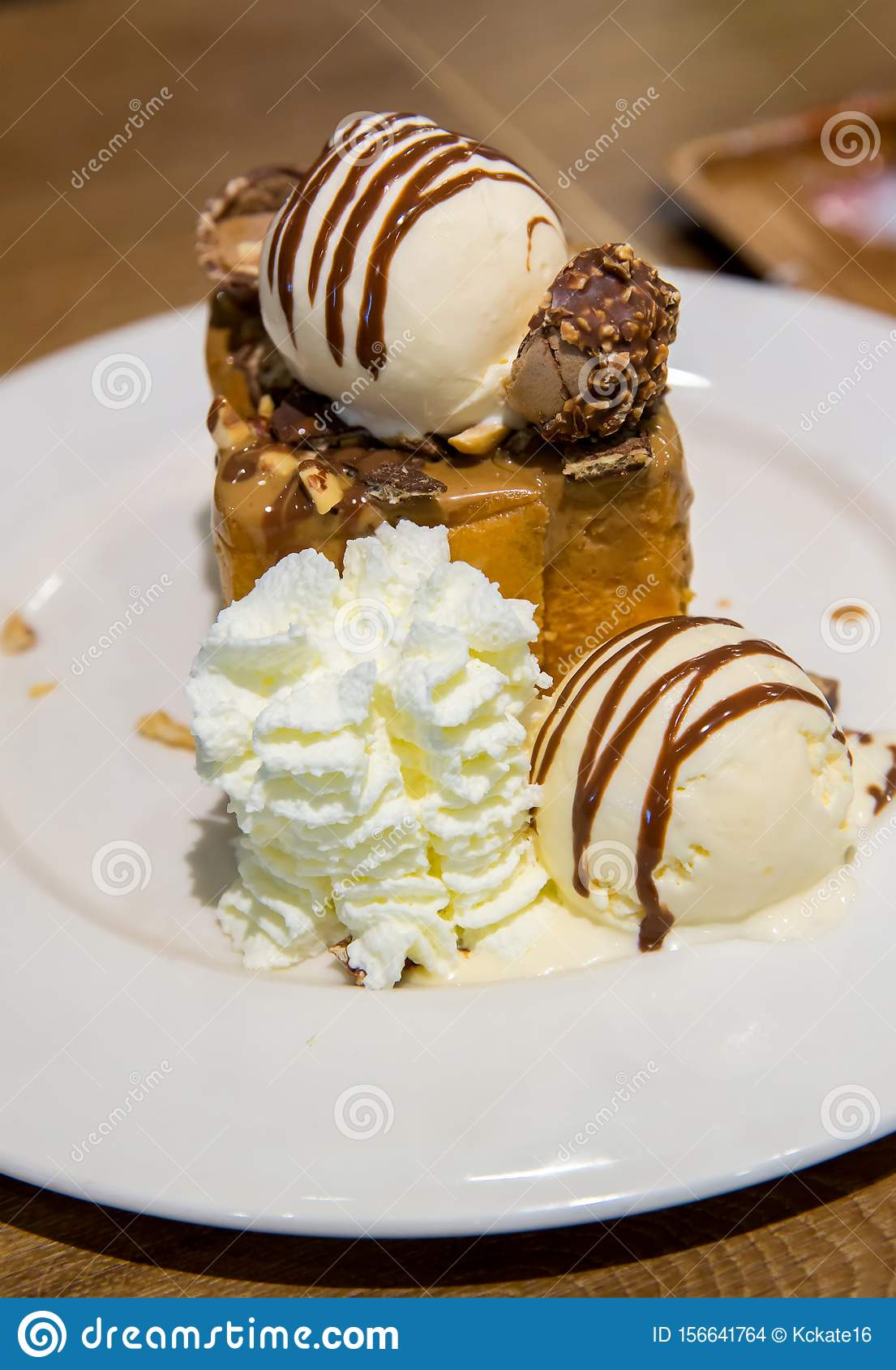 Honey toast with vanilla ice cream and whiping cream topped with chocolate sauce on white dish. sweets bread and dessert.