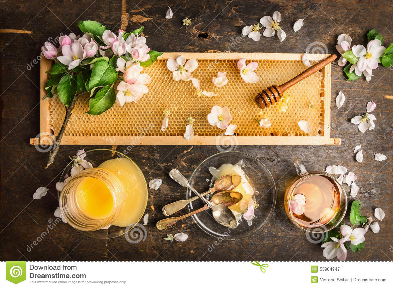 Honeycomb with wooden dipper and fresh blossom, jar with honey and plate with vintage spoons