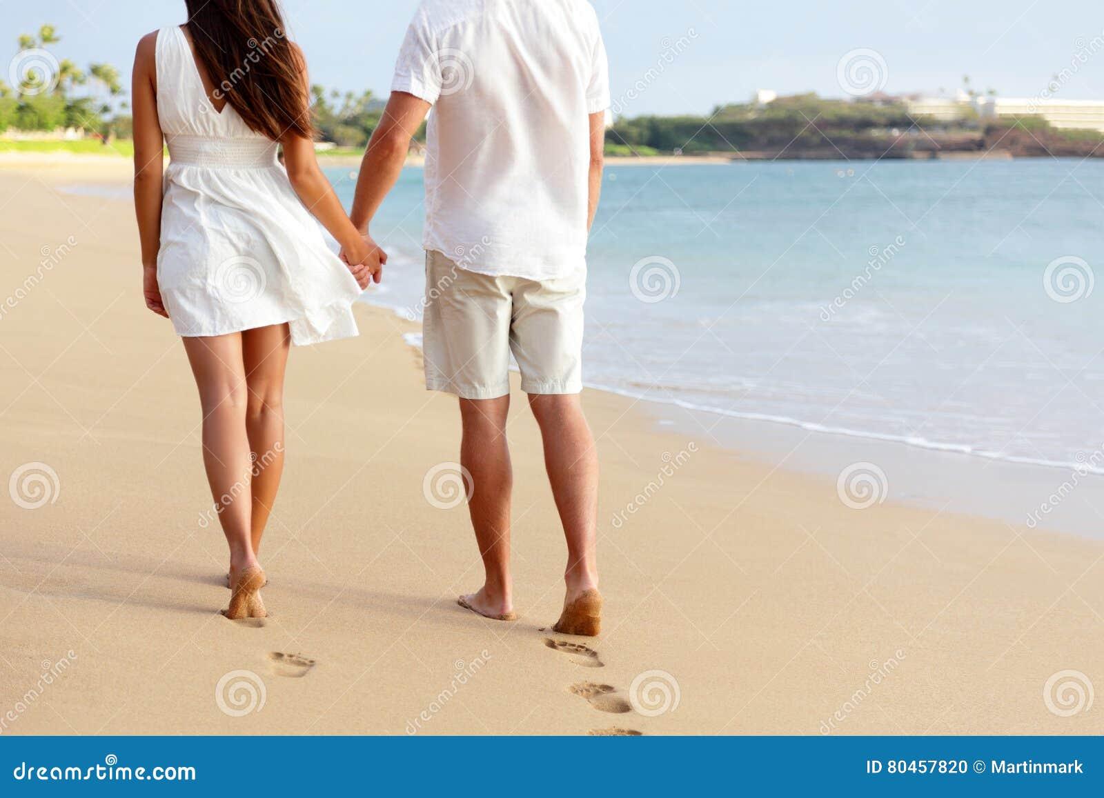 Honeymoon couple holding hands walking on beach stock for Honeymoon on the beach