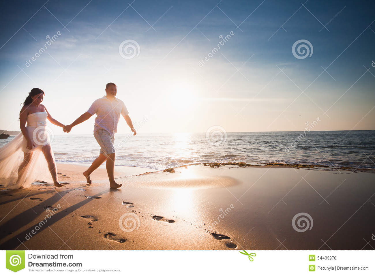 Honeymooners couple just married running at beach stock photo royalty free stock photo kristyandbryce Images