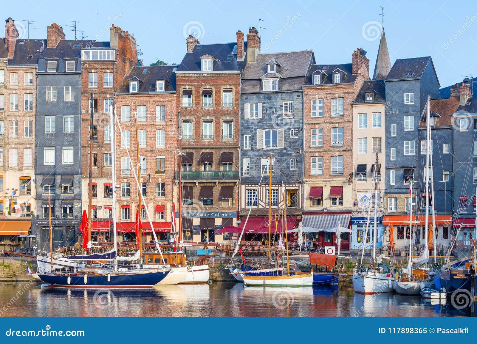 Honfleur Frankrike - Augusti 31, 2016: Pittoresk gammal hamn på den Normandie byn av Honfleur Frankrike med fartyg och kaféer