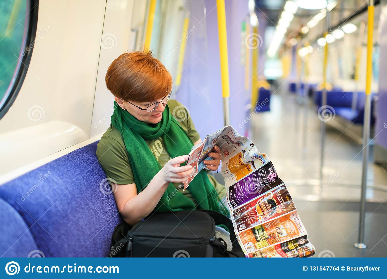 HONG KONG april 2018 - Woman sitting in train and studying route map. Caucasian tourist in wagon of metro. traveler in the subway