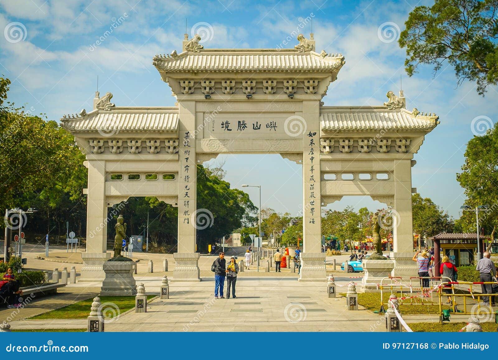 HONG KONG, CHINA - 26 DE JANEIRO DE 2017: Povos não identificados que andam na porta da entrada ao monastério de Tian Tin e ao gr