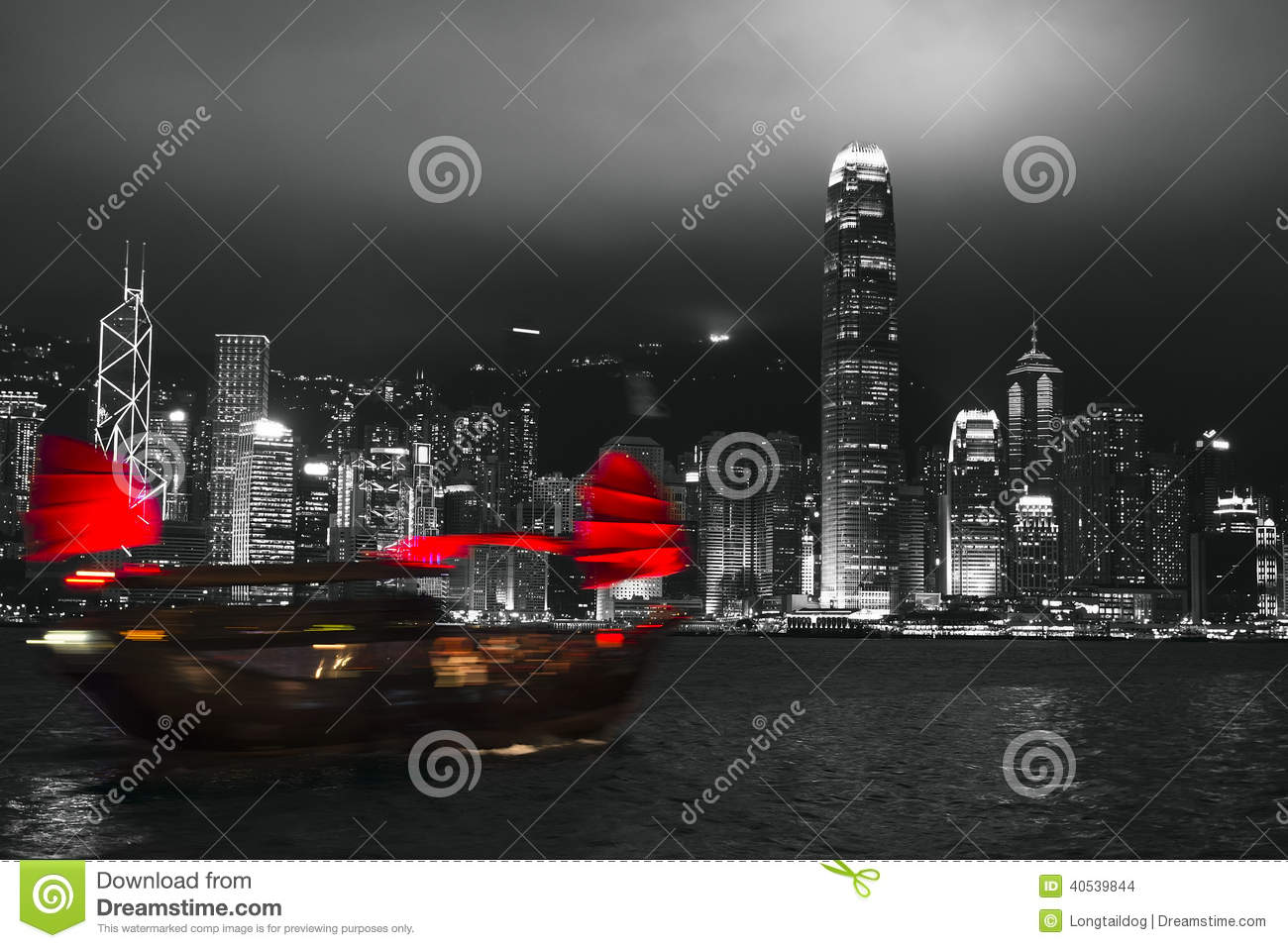Hong Kong harbor at night with blurred silhouette of sailboat