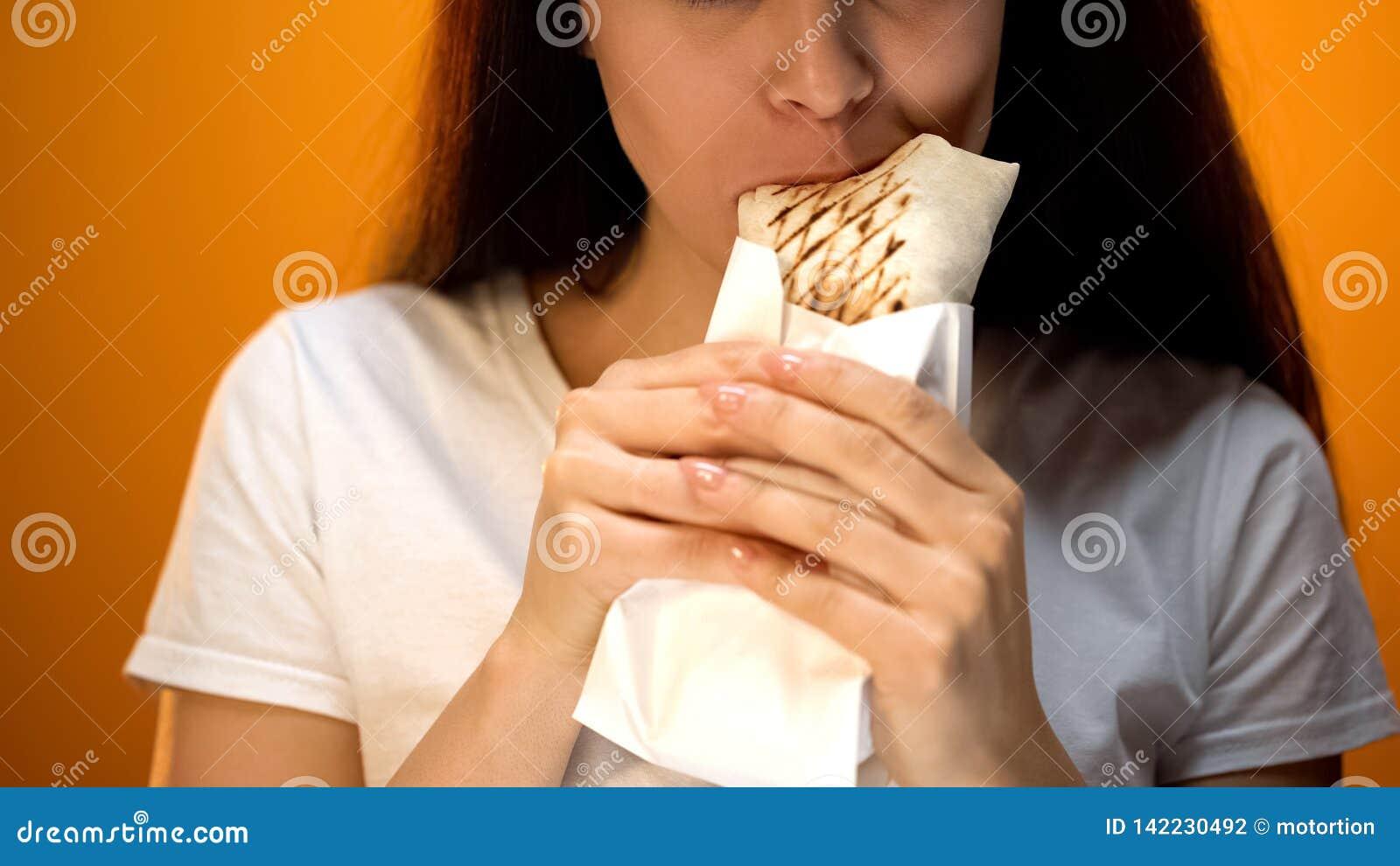 Hongerig meisje die shawarma eten, die van heerlijk maar ongezond voedsel, verslaving genieten