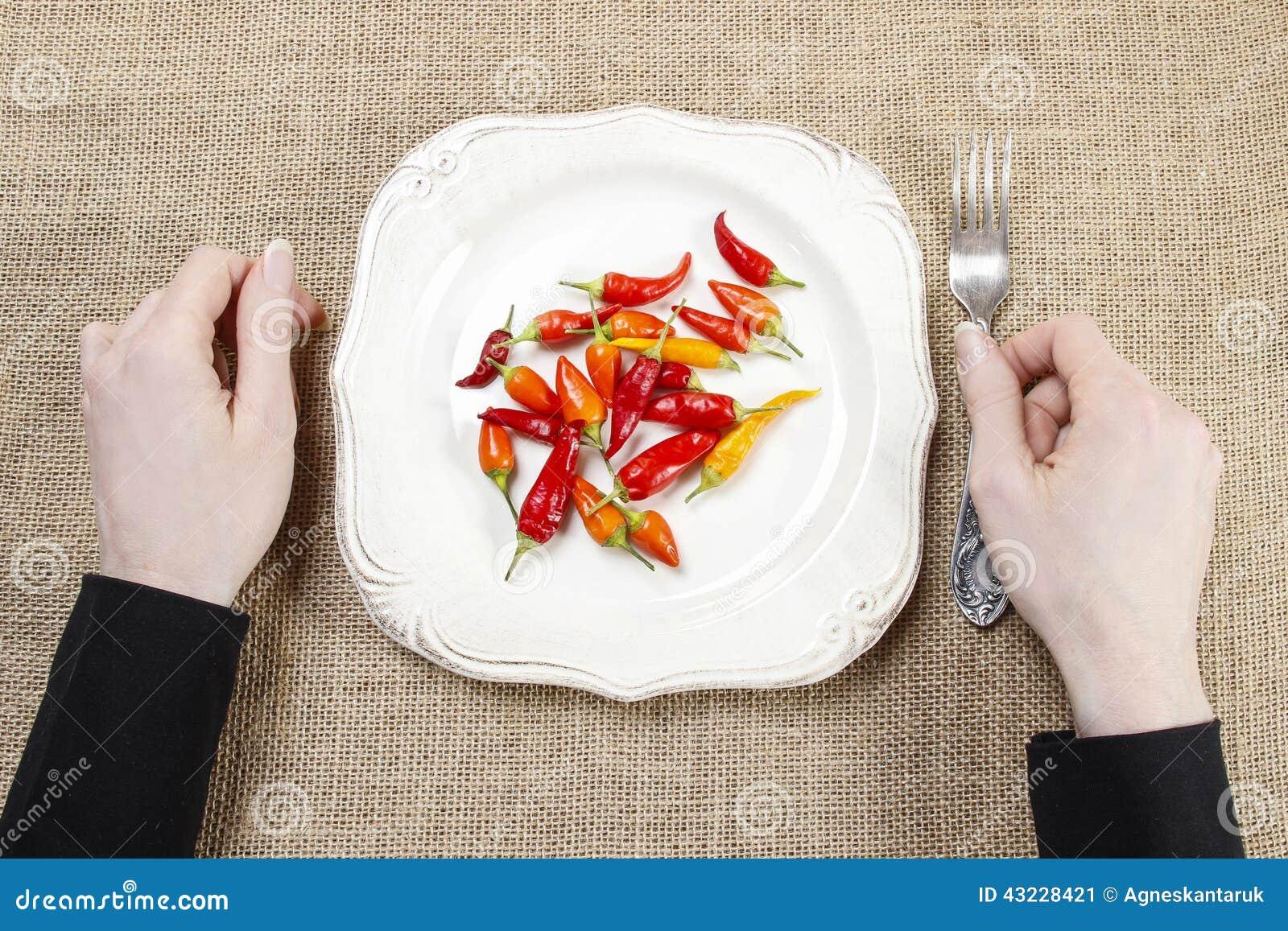 Hongerige vrouw die roodgloeiende Spaanse peperpeper eten Symbool van het aanpassen aan