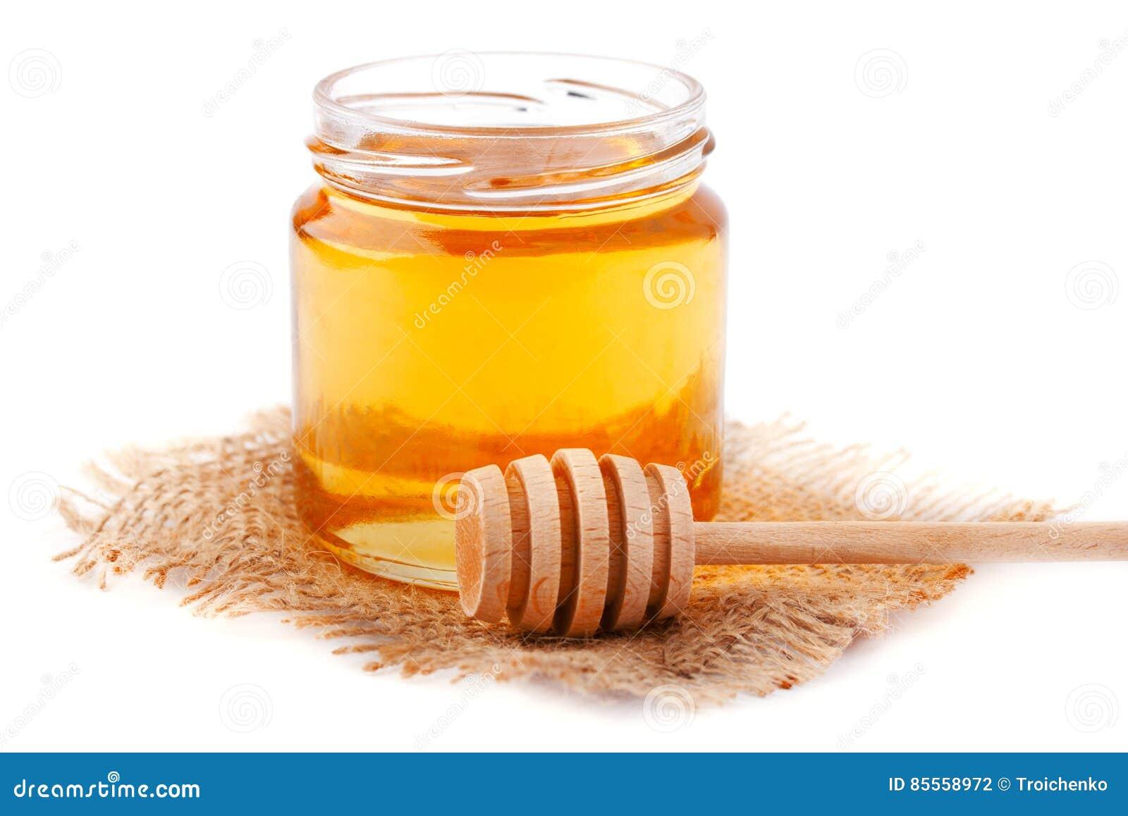 Honig im Glas mit einem hölzernen Löffel lokalisiert auf Weiß